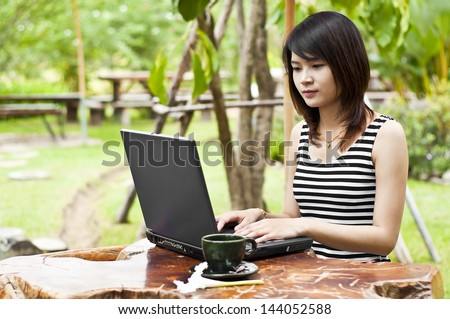 Beautiful Asian woman working with notebook and coffee.