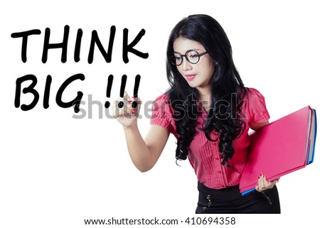 Beautiful Asian woman writing a text of Think Big on the whiteboard while holding folder, isolated on white background - stock photo