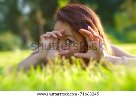 Beautiful asian womanl lays in a field - stock photo