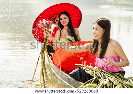 Beautiful asian women wear traditionnel thai dress sitting on wood boat and collect the lotus from the river with water splash in the morning
