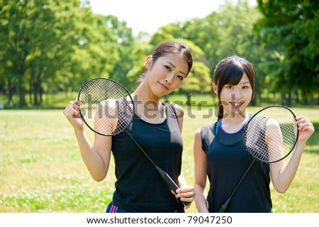 beautiful asian women with racket in the park - stock photo