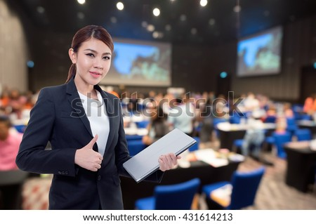 Beautiful asian working woman on the Abstract  blurred photo of conference hall or seminar room with attendee background.