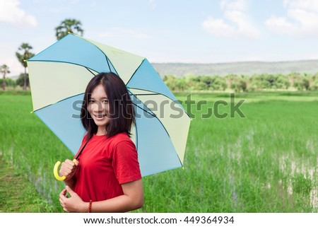 Beautiful asian young girl holding umbrella on green rice field and blue sky.