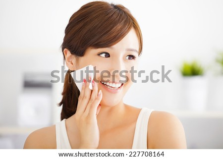 Beautiful asian young woman cleaning her face with cotton