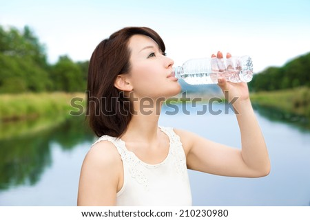 Beautiful asian young woman drinking a bottle of water in the nature.  - stock photo