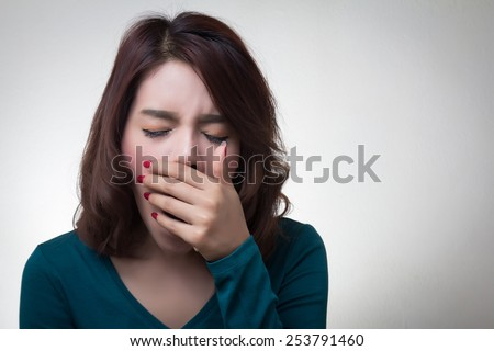 beautiful asian young woman placing hand covering mouth yawning