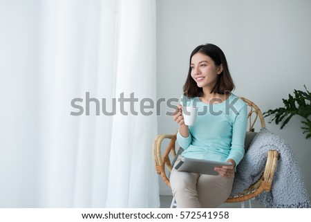 Beautiful asian young woman relaxing and using digital tablet at home