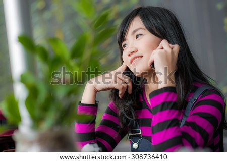Beautiful asian young woman speaking by mobile phone at art coffee shop, Smiling woman