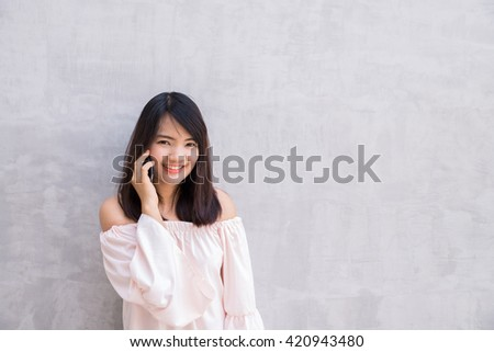 Beautiful asian young woman talking on Mobile Phone, over concrete wall - stock photo
