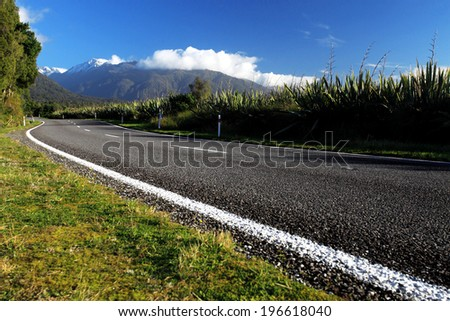 Beautiful asphalt highway curve road to the mountain in summer New Zealand - stock photo