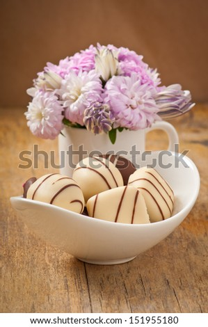 Beautiful aster flower bouquet and chocolates on wooden table - stock photo