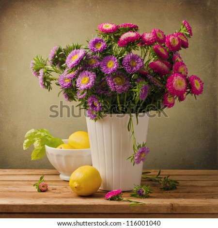 Beautiful aster flower bouquet with lemons on wooden table - stock photo