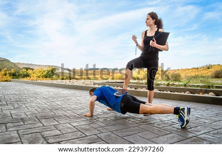 Beautiful athlete girl coach training very hard a man while timing the push ups with chronometer - stock photo