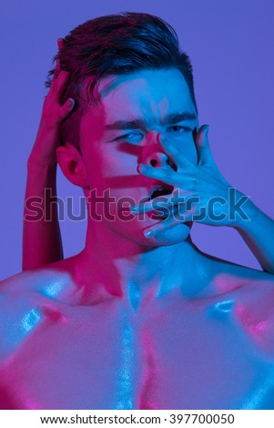 Beautiful athletic bodybuilder male model posing in studio. Muscular healthy sexy body. Expression on camera. Mixed light.