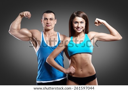 Beautiful athletic couple on gray background isolated with clipping path - stock photo
