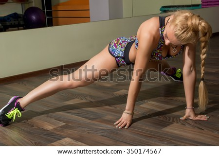 Beautiful athletic girl doing the splits in the gym