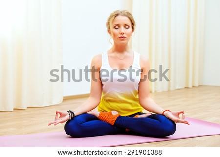 Beautiful athletic girl doing yoga exercises indoor. Lotus pose. Meditation. - stock photo