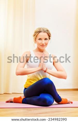 Beautiful athletic girl doing yoga exercises indoor. Meditation. - stock photo