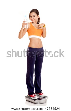 Beautiful athletic girl over a scale, isolated on white - stock photo