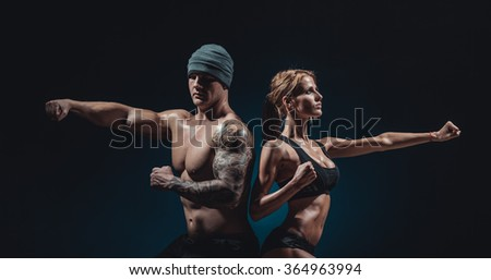 beautiful athletic man and woman posing on black background - stock photo