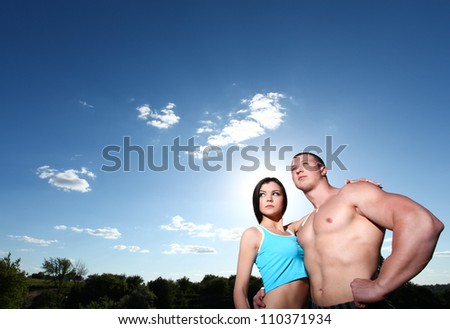 Beautiful athletic man and woman standing in embrace against the blue sky - stock photo