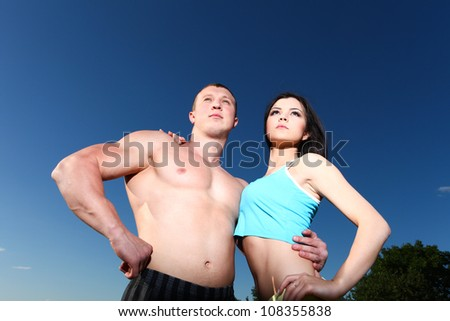 Beautiful athletic man and woman standing next to each other against the blue sky - stock photo