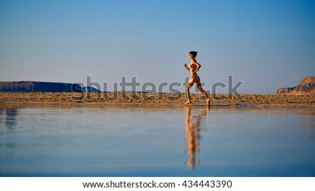 beautiful athletic woman dressed in bikini running on the beach along the sea front at the sunset  - stock photo