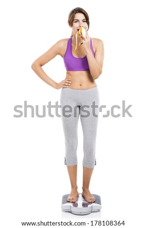Beautiful athletic woman over a scale and eating a banana, isolated over white background