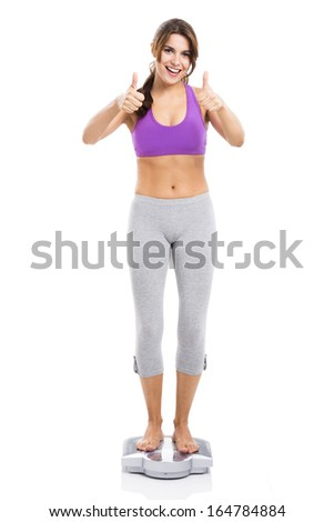 Beautiful athletic woman over a scale with thumbs up, isolated over white background - stock photo