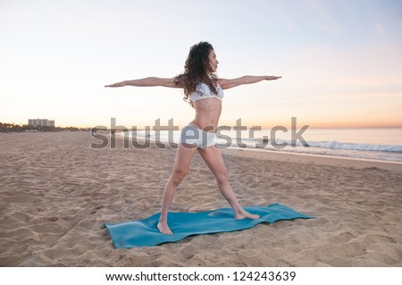 Beautiful athletic woman practicing energizing and relaxing yoga exercises on a colorful sunrise on the beach