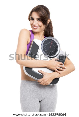 Beautiful athletic woman smilling and holding a scale, isolated on white - stock photo