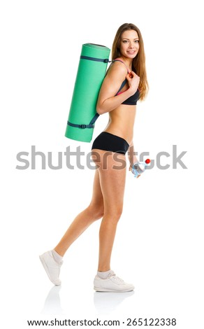 Beautiful athletic woman with mat for fitness and bottle of water standing on white background - stock photo