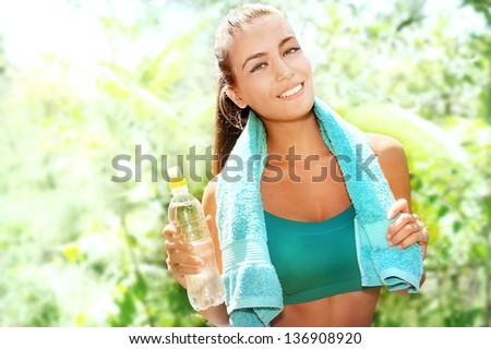 Beautiful athletic woman with plastic bottle of water - stock photo