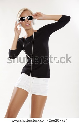 Beautiful attractive and sensuality young adult pretty blonde woman is listen to the music in white headphones and sunglasses - stock photo