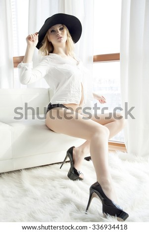 Beautiful attractive and sexy young adult sensuality pretty blonde woman in white shirt black hat and panties on the white sofa and morning sunlight window in luxury apartment - stock photo