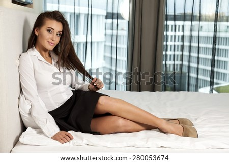 Beautiful attractive and sexy young adult sensuality pretty brunette woman in black and white elegance dress on the bed in hotel room - stock photo