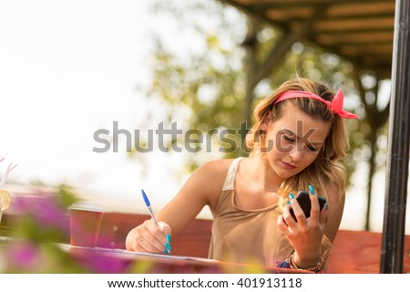 Beautiful attractive blond girl sitting in an outdoor cafe, texting on her mobile phone and writing notes - stock photo