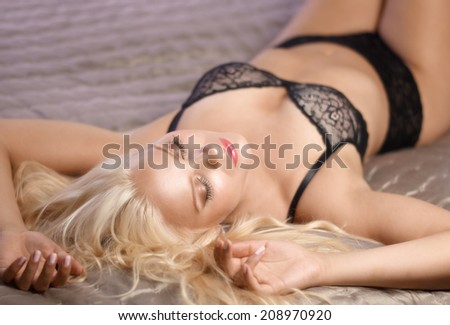 Beautiful attractive blond woman wearing lingerie and lying on the bed - stock photo