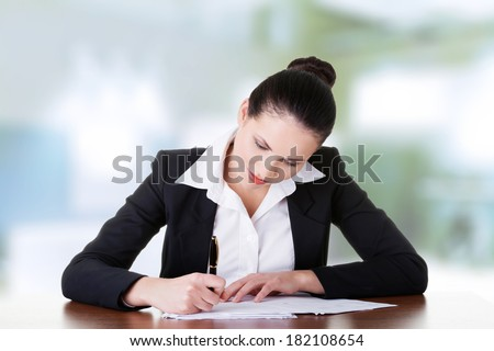 Beautiful attractive corporate lawyer business woman sitting at desk and writing blank paper page - stock photo