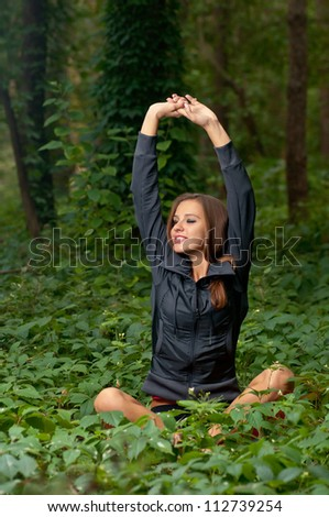 Beautiful attractive girl meditating outdoors in lotus pose - stock photo