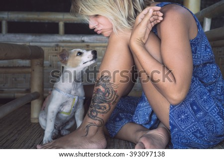 beautiful attractive girl with a tattoo on his leg a little puppy kisses on the nose  - stock photo