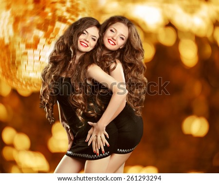Beautiful attractive laughing two girls dancing over holiday discolight background. Pretty women with long wavy hair in black short dress. - stock photo