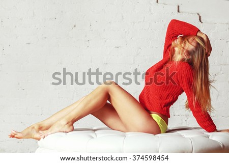 beautiful attractive sexy and sensuality young blonde woman long legs in red sweater. Fashion style photoshoot