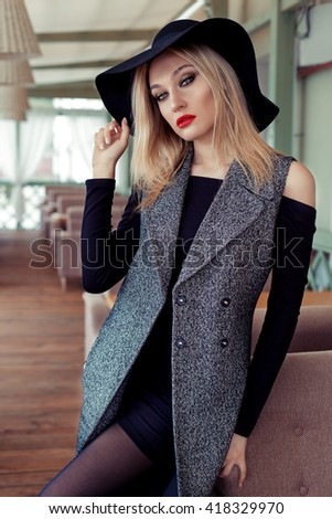 beautiful attractive sexy blond girl in a cafe in a black hat and coat with trendy makeup smokey eyes