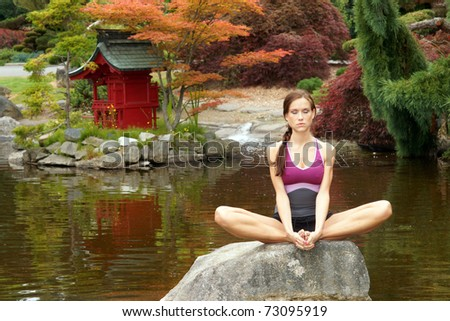 Beautiful Attractive Woman Meditates on Sitting on Rock in a Beautifully Landscaped Pagoda Pond - stock photo
