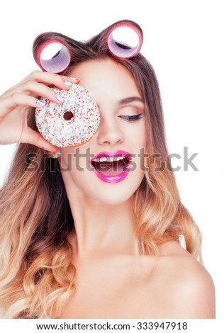 Beautiful attractive young caucasian girl with pink curlers on her hair taking a sweet cake.