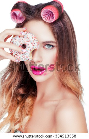 Beautiful attractive young caucasian girl with pink curlers on her hair taking a sweet cake. - stock photo