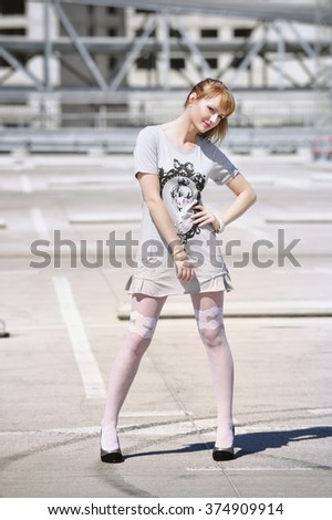 Beautiful attractive young female in summer dress posing to the camera. Cute girl with sexy body posing outdoors. - stock photo