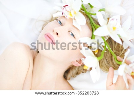 Beautiful attractive young woman (close up face) with white caucasian healthy skin, blond hair, blue eyes and glamour lips, lily flowers. Model appearance, fashion look - stock photo