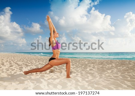 Beautiful attractive young woman exercising yoga on the empty beach in the morning - stock photo